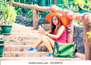 Filipino young tourist woman holding mobile phone sitting on old house steps at summer day - Holiday portrait of hippy girl with hat and shorts - Vintage concept of tropical vacation and youth fashion