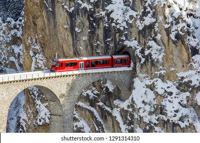 Filisur, Switzerland - January 19. 2019: A red Swiss train is coming out of the tunnel of the Landwasser Viaduct, a wonder of Swiss mountain railway engineering. A unesco site.