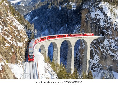 Filisur, Switzerland - January 19. 2019: A red passenger Swiss train passing on the Landwasser Viaduct, which ia a wonder of Swiss mountain railway engineering in 190, a unesco heritage since 2008.