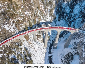 Filisur Switzerland - January 31. 2019: A red passenger Swiss train passing on the famous Landwasser Viaduct - an aeiral image by drone