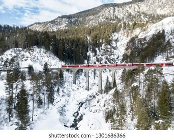 Filisur Switzerland - January 31. 2019: A red passenger Swiss train passing on the Schmitten viaduct, which is on the same line with Landwasser Viaduct