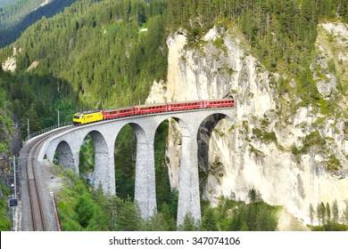 FILISUR, SWITZERLAND - JUNE 21, 2015: Landwasser Viaduct with train. Designed by Alexander Acatos, it was built between 1901 and 1902 by Müller & Zeerleder for the Rhaetian Railway. Rhaetian railway