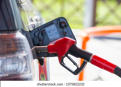 Fill the car with fuel. The car is filled with gasoline at a gas station. Gas station pump. Man refueling gasoline with fuel in a car, holding a nozzle. Limited depth of field. Blurred image Close-up.