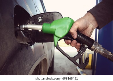 Fill up fuel at petrol station. Filling a dirty car at a gas station. Fuelling nozzle for refuelling a car in man's hand.