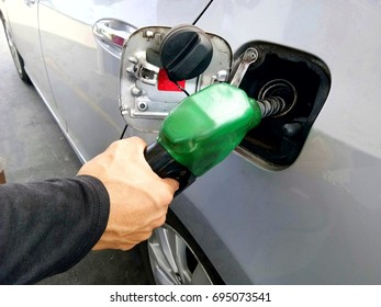 fill up the gas tank. a man pumping  gasoline into the tank