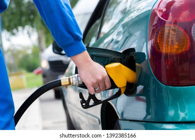 To fill the machine with fuel.   Gas station pump. Man filling gasoline fuel in car holding nozzle