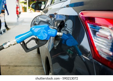 To fill the machine with fuel. Gas station pump. Man filling gasoline fuel in car holding nozzle. Close up.