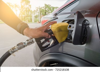 fill up with petrol in gas station by person .