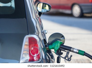 fill up with petrol in pumping gas, pumping fuel nozzle gasoline fuel at gas station background.