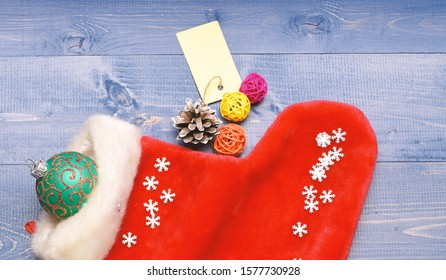 Fill sock with gifts or presents. Celebrate christmas. Small items stocking stuffers or fillers little christmas gifts. Contents of christmas stocking. Christmas sock toned wood background top view.