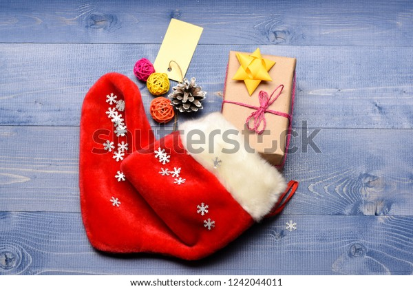 Fill sock with gifts or presents. Celebrate christmas. Contents of christmas stocking. Small items stocking stuffers or fillers little christmas gifts. Christmas sock toned wood background top view.