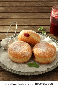 Filled Berliner style donuts / doughnut with Raspberry Jam Dusted with Icing Sugar. selective focus on rustic table
