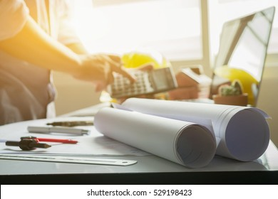 filled with building and Town planning,architect man working with laptop and blueprints, architectural plan with calculator in loft office,Building Design,selective focus.