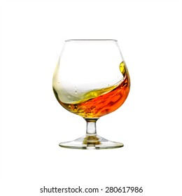 A filled cognac snifter with moving liquid isolated on white