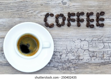 Filled espresso cup with text coffee out of beans from above