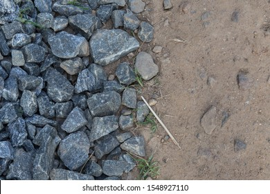 filled frame split in half detailed close up wallpaper background shot of a pile of dark grey gravel ballast stones on one side and brown beige dusty sand and earth ground surface on the other