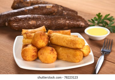 Filled fried balls and sticks out of manioc with a dip and some manioc roots in the back (Selective Focus, Focus on the manioc balls and the manioc sticks in the front)