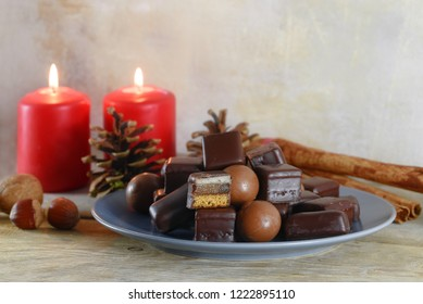 filled gingerbread cookies, in germany called domino steine, chocolate balls and red candles for Advent and Christmas on a rustic wooden table, copy space, selected soft focus, narrow depth of field