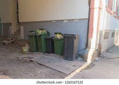 Filled rubbish bins are in a driveway