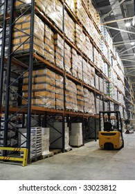 filled shelf with different productions in the cardboard boxes in the huge storehouse with constructions and loader