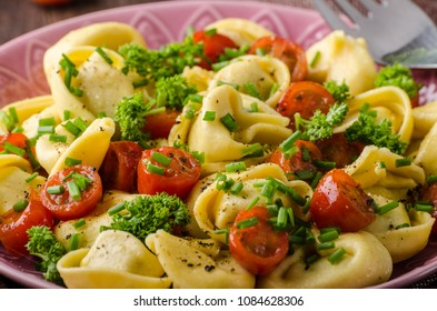 Filled tortellini with herbs, tomatoes, fresh cheese, food photography, product photo
