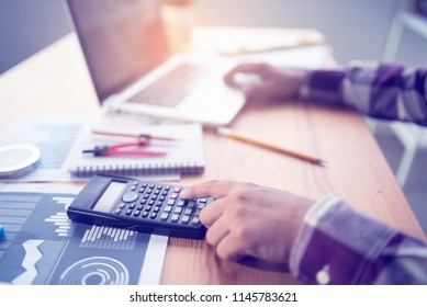 filled with Town planning,engineer people, architect man using calculator for accounting and analyzing building structure from blueprint,paper chart  with computer laptop at modern office workspace