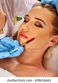 Filler injection for female forehead face. Plastic aesthetic facial surgery in beauty clinic. Beauty woman giving injections. Doctor in medical gloves with red syringe injects cheeks drug.