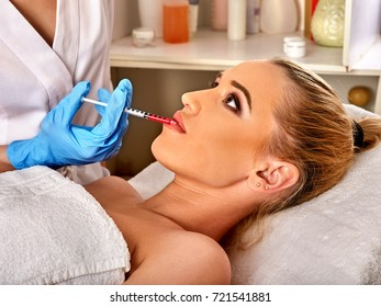 Filler injection for female lip face. Silicone lips in girl. Doctor in medical gloves with syringe injects lips augmentation.