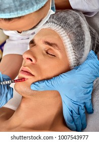 Filler injection for male face. Plastic aesthetic facial surgery in beauty clinic. Man giving anti-aging injections for face contour . Doctor hand in medical gloves with syringe injects drug.
