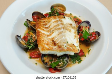 Fillet of Cod over Mashed Potatoes, with clams on a half shell.