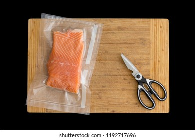 Fillet of fresh Atlantic salmon packaged fro freezing in a vacuum pack of clear plastic lying on a wooden board with scissors viewed from above