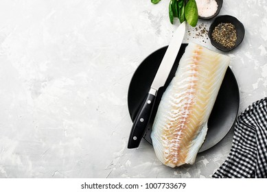 Fillet of fresh sea cod to prepare a healthy healthy dish with salt, ground pepper, fresh seasonal greens, lemon slices on the background with a kitchen knife for cutting. Copy space