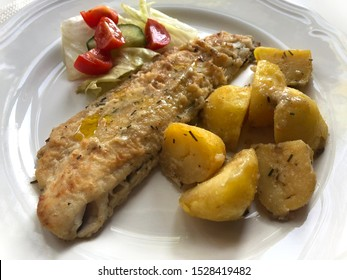 "Fillet of fried pike perch fish or ""Zander fillet"" with fried potatoes and salad bouquet."