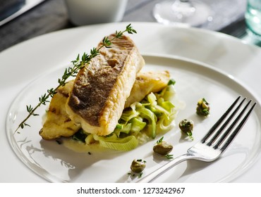 Fillet of halibut on a pillow of stewed leeks on the white plate