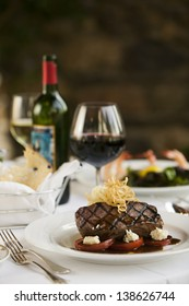 A fillet mignon steak dinner with a bottle and glass of red wine in a fine restaurant setting.