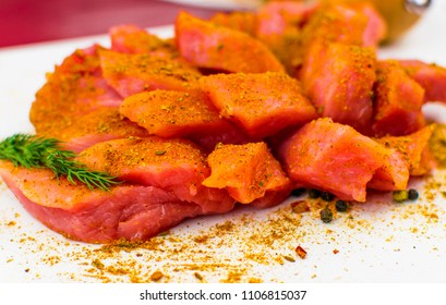 Fillet of pork chopped slices sprinkled with spices on a white background.