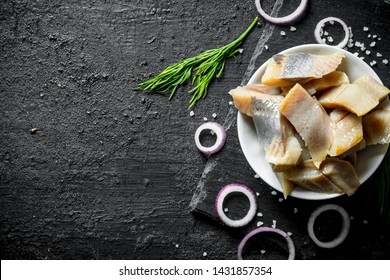 Fillet of salted herring with dill and chopped onion. On black rustic background