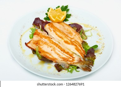 Fillet of sea bass grilled with rocket and lemon,  isolated on white background