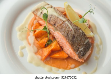 Fillet of Trout fillet grilled with carrots and mashed sweet potatoes on a plate