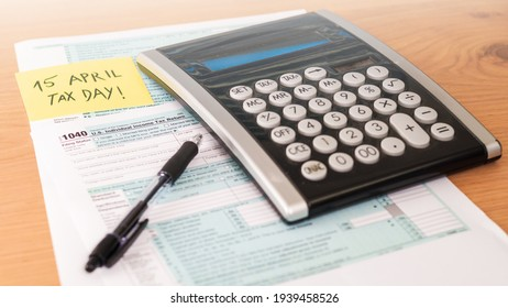 Filling 1040 form on tax day with calculator on table to be returned. American event.