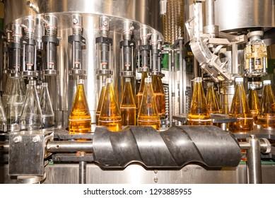 Filling  glass bottles with juice. Bottling of drinks. bottling plant