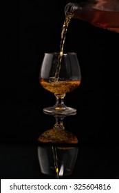 filling a glass of brandy on a black background.