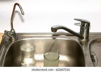 Filling a glass of clean and muddy water from a filter and a kitchen faucet