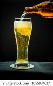 Filling glass glass with golden beer on black background