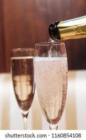 Filling a glass with Prosecco sparkling wine in an elegant restaurant in Valdobbiadene