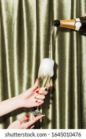 Filling a glass with sparkling Prosecco di Conegliano-Valdobbiadene, held by girl's hands.