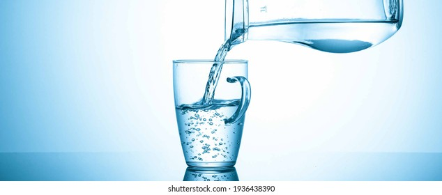 Filling a glass with water from a jug on a blue background