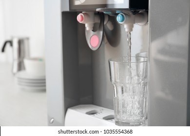 Filling glass with water from modern cooler, closeup