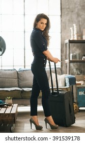 Filling inspired for adventure! Full length portrait of elegant woman with passport, ticket and luggage in loft apartment ready for departure. Holiday and travel concept