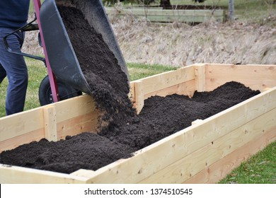 Filling a newly constructed backyard garden box with soil.